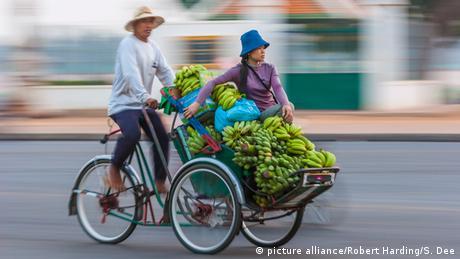 Frau auf Rikscha mit Bananen (Foto: picture alliance/Robert Harding/S. Dee)