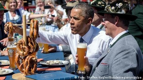 Barack Obama & ein Mann in bayerischer Tracht essen Brezeln und trinken Bier dazu