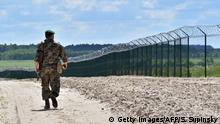 TO GO WITH AFP STORY BY DMYTRO GORSHKOV A Ukrainian border guard patrols on July 2, 2015 along the barbed wire fence on the Senkivka border post, around 200 kilometres (125 miles) north of the Ukrainian capital Kiev. The freshly-dug ditch running along a short stretch of metal fence topped with barbed wire marks the start of a new border defence that Ukraine hopes will protect it from Russia. Dubbed the Wall, the ambitious project to seal up Ukraine's porous 2,000-kilometre frontier with it's ex-Soviet neighbour was announced in March 2014 after Moscow seized the Crimea peninsula from Kiev. AFP PHOTO / SERGEI SUPINSKY (Photo credit should read SERGEI SUPINSKY/AFP/Getty Images)