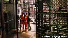 GUANTANAMO BAY, CUBA - OCTOBER 27: (EDITORS NOTE: Image has been reviewed by U.S. Military prior to transmission.) A 'non-compliant' detainee is escorted by guards after showering inside the U.S. military prison for 'enemy combatants' on October 27, 2009 in Guantanamo Bay, Cuba. Although U.S. President Barack Obama pledged in his first executive order last January to close the infamous prison within a year's time, the government has been struggling to try the accused terrorists and to transfer them out ahead of the deadline. Military officials at the prison point to improved living standards and state of the art medical treatment available to detainees, but the facility's international reputation remains tied to 'enhanced interrogation techniques' such as waterboarding employed under the Bush administration. (Photo by John Moore/Getty Images)