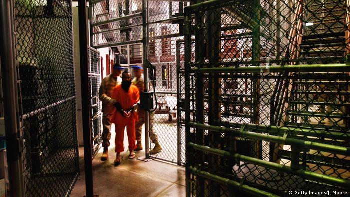 A prisoner being escorted by military personnel at the Guantanamo Bay detention center