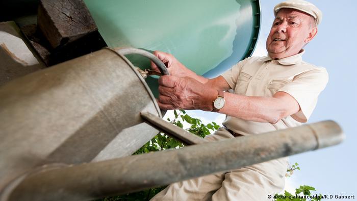 Ein Mann füllt seine Gießkanne mit Wasser aus der Regentonne (Foto:dpa/K.D.Gabbert)