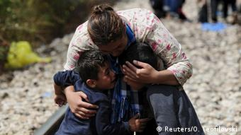 A woman hugs two boys Saturday after crossing Greece's border into Macedonia.