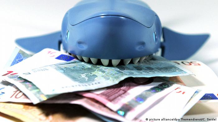 A plastic shark eating banknotes