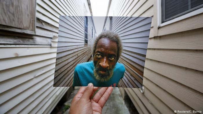 Im Foto im Foto ein älterer Afroamerikaner zwischen zwei Hauswänden. Sein Blick fällt auf die linke Hauswand. (Foto: REUTERS/Carlos Barria)