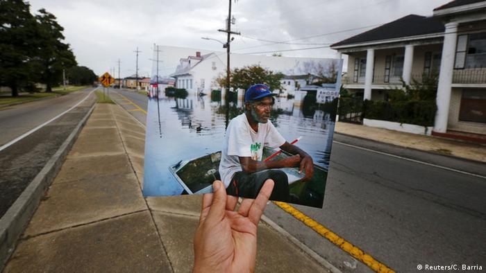 Auf dem Bild im Bild ein äterer schwarzer Mann in einem Bott inmitten eines überschwemmten Wohnviertels. Dahinter im Bild das Viertel heute - eine Straße ist wieder sichtbar, Häuser und Bäume säumen diese Straße. (Foto: REUTERS/Carlos Barria)
