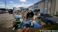 Photographer Carlos Barria holds a print of a photograph he took in 2005, as he matches it up at the same location 10 years on, in North Shore, northwest of New Orleans, United States, August 17, 2015. The print shows Michael Rehage squatting on the roof of his car, September 12, 2005, after Hurricane Katrina struck. In 2005, Hurricane Katrina triggered floods that inundated New Orleans and killed more than 1,500 people as storm waters overwhelmed levees and broke through floodwalls. Congress authorised spending more than $14 billion to beef up the city's flood protection after Katrina and built a series of new barriers that include manmade islands and new wetlands. After photographing events a decade ago, Reuters photographer Carlos Barria returned to New Orleans. Using photos he took 10 years ago, Barria found the same locations that he documented originally and used the photos he took in 2005 to show the contrast of inundation then and a city now still affected by the disaster. REUTERS/Carlos BarriaPICTURE 6 OF 9 FOR WIDER IMAGE STORY KATRINA SCENES OVERLAIDSEARCH CARLOS KATRINA FOR ALL IMAGES