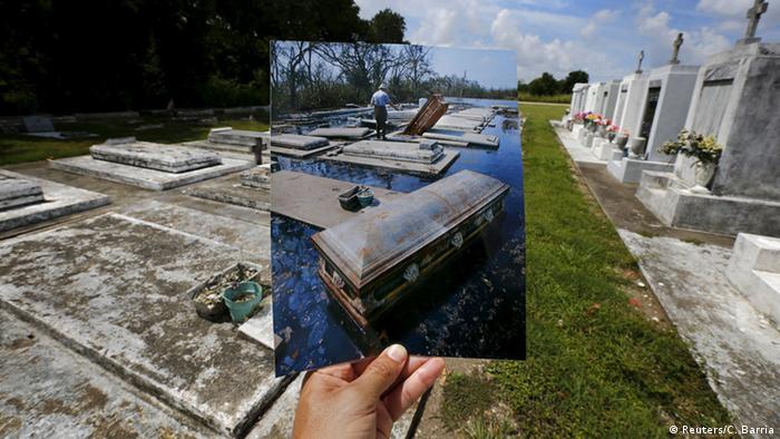 Auf dem Bild von 2005 zu sehen: Ein überschwemmter Friedhof, in der Mitte des Bildes ein Sarg, der im Wasser schwimmt. Heute ist der Friedhof trocken - und einige Gräber im Hintergrund sind mit frischen Blumen versehen worden. (Foto: REUTERS/Carlos Barria)