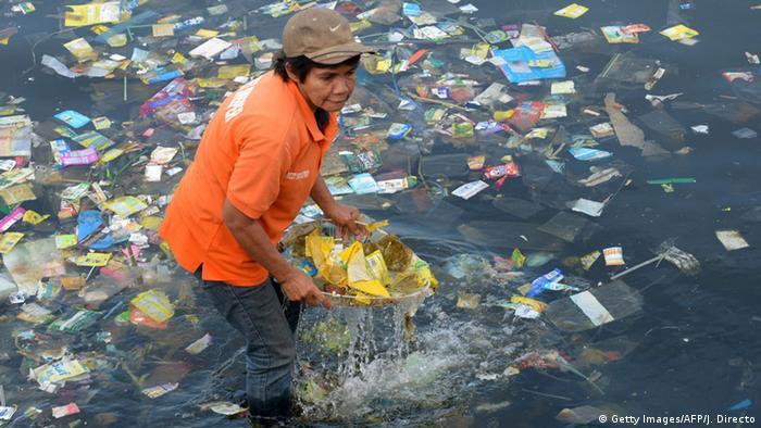 Eine Frau fischt Plastikmüll aus dem Meer