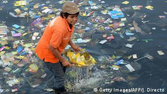 A man collects plastic from waters of Manila Bay (photo: JAY DIRECTO/AFP/Getty Images)