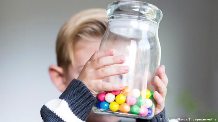 Criança com um vidro de balas coloridas