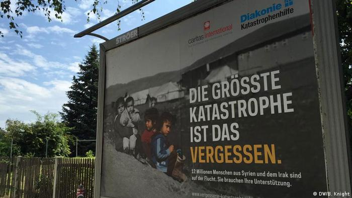 A poster for a charity helping refugees seen at a bus shelter in Heidenau
