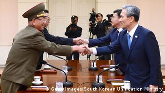 In this handout image provided by South Korean Unification Ministry, South Korean National Security Adviser Kim Kwan-Jin (R), South Korean Unification Minister Hong Yong-Pyo (2nd R), Kim Yang-Gon (2nd L), the top North Korean official in charge of inter-Korean affairs, and Hwang Pyong-So (L) the North Korean military's top political officer, shake hands during the inter-Korean high-level talks at the truce village of Panmunjom inside the Demilitarized Zone on August 22, 2015 (Photo: South Korean Unification Ministry via Getty Images)