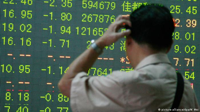 Chinese investor looking at stock board