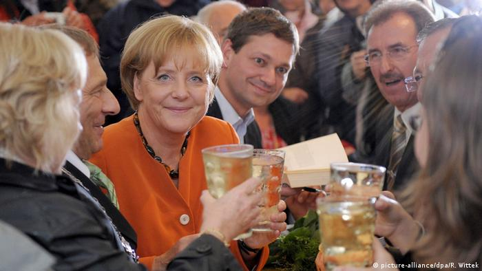 Angela Merkel surrounded by people , glass of wine in hand (picture-alliance/dpa/R. Wittek)