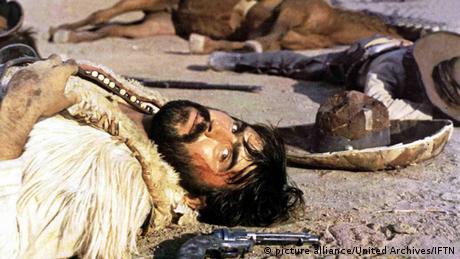 Mario Adorf in einer Sterbeszene in dem Film Fahrt Zur Hölle, Ihr Halunken am Boden neben Pistole ((Foto: picture alliance Untitled Archives FTN)