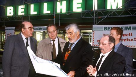 Mario Adorf mit mehreren Darsteller in dem Film Der große Bellheim, Adorf in der Mitte präsentiert auf großen Papierbögen Architekturpläne (Foto: picture alliance dpa S. Hesse)