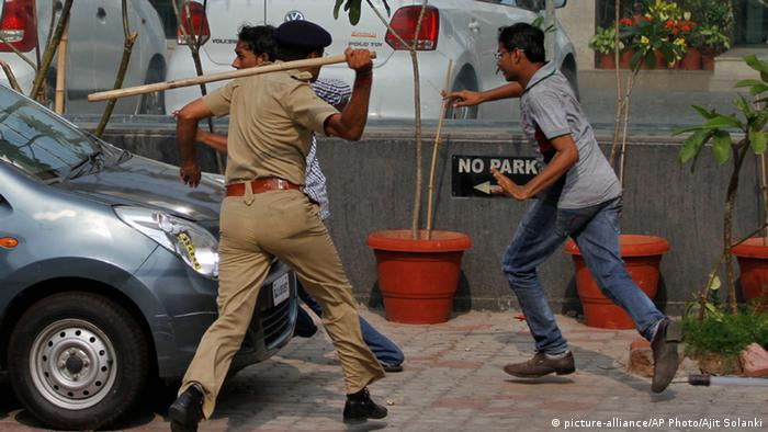 An Indian policeman uses a baton to disperse protesters during a clash between two groups in Ahmadabad, India, Tuesday, Aug. 25, 2015 (AP Photo/Ajit Solanki)