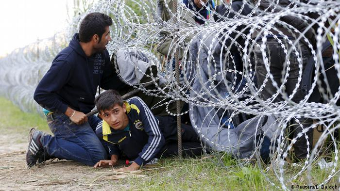 Syrian migrants cross under a fence into Hungary at the border with Serbia, near Roszke, August 26, 2015 (Photo: REUTERS/Laszlo Balogh)