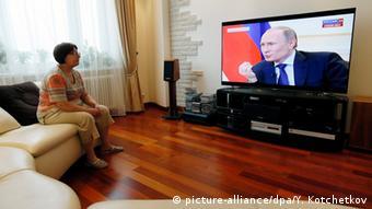Женщина смотрит по телевизору выступление Путина