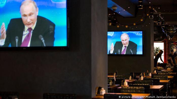 Wladimir Putin auf Fernsehbildschirmen während einer Pressekonferenz im Dezember 2014.