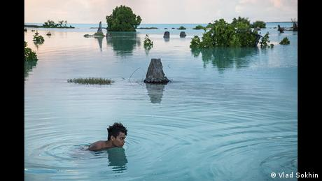 A young man in floods in Kiribati (Photo: Vlad Sokhin)