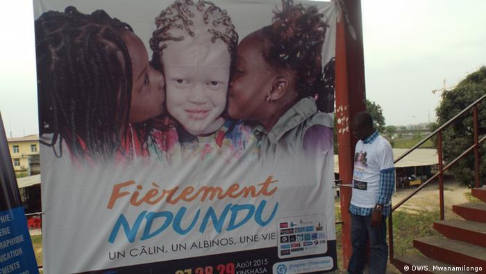 Ein Besucher blickt auf das Plakat der Veranstaltung: Darauf küssen zwei schwarze Mädchen ein Albinokind auf die Wangen