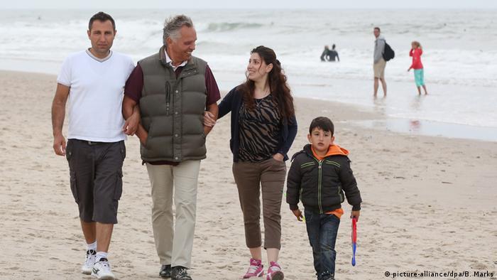 Eine Flüchtlingsfamilie aus Syrien spaziert mit dem ehrenamtlichen Helfer Joachim Leber am Strand auf Sylt Foto: picture-alliance/dpa/B. Marks