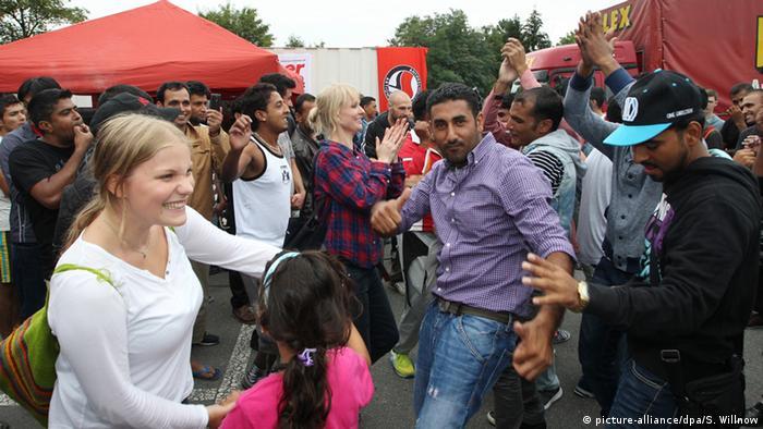 Flüchtlinge und Unterstützer tanzen gemeinsam auf einem Willkommensfest für Flüchtlinge in Heidenau Foto: picture-alliance/dpa/S. Willnow