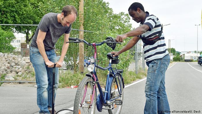 Tobias Fleiter von der Initiative bikes without borders pumpt in Karlsruhe für einen den Reifen eines Fahrrads auf Foto: picture-alliance/dpa/U. Deck