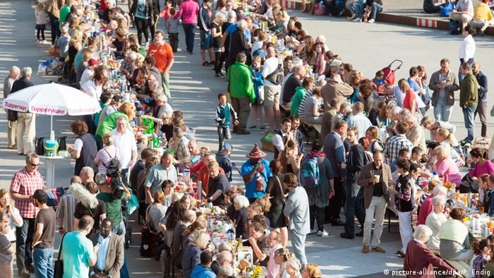 Zahlreiche Bürger sitzen mit Flüchtlingen beim gemeinsamen Frühstück in Halle zusammen Foto: picture-alliance/dpa/P. Endig