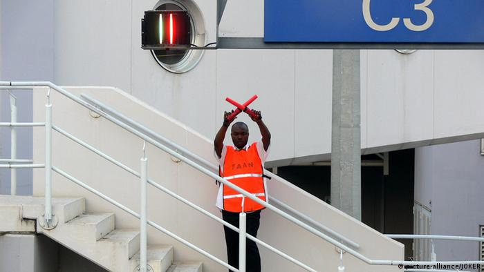 A man on the stairs leading to a plane at Abuj