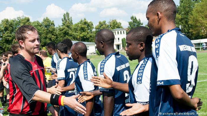 Henning Eich von ESV Lok Potsdam II begrüßt am Fußballplatz die Spieler von Deutschlands erster Flüchtlingsmannschaft Foto: picture-alliance/dpa/O. Mehlis