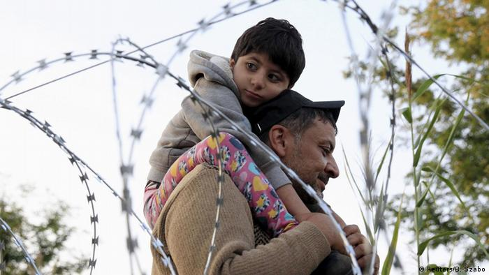 A Syrian migrant with a boy on the Serbian side of the border with Hungary (2015) (Reuters/B. Szabo)