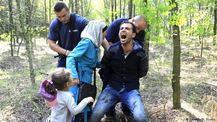 Refugee family being arrested REUTERS/Bernadett Szabo