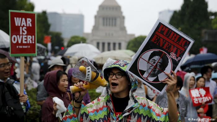 People hold placards and shout slogans as they protest against Japan's Prime Minister Shinzo Abe's security bill outside parliament in Tokyo August 30, 2015 (Photo: REUTERS/Thomas Peter)