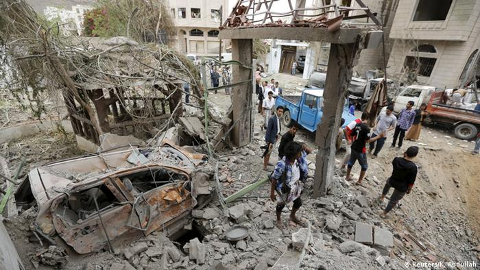 Residents assess the damage after a Saudi-led raid in the capital, Sanaa