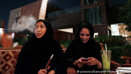 Saudi Arabian women use their phones and smoke tobacco (picture-alliance/AP Photo/H. Ammar)