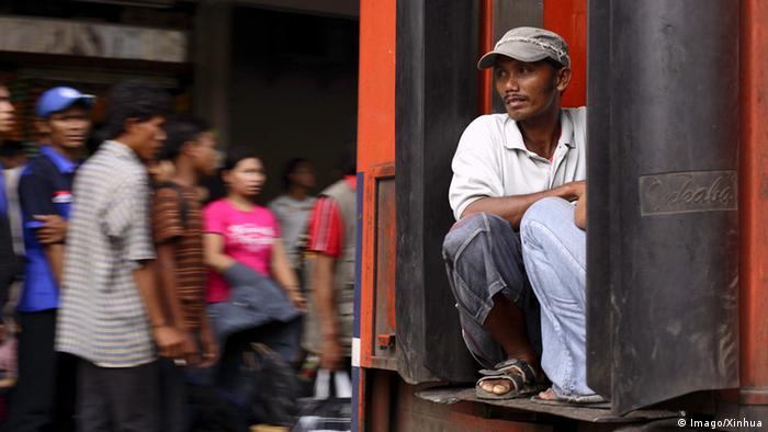 Ein Mann hockt hinten auf dem Trittbrett einer Straßenbahn