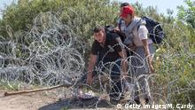 30.08.2015+++ SZEGED, HUNGARY - AUGUST 30: Migrants scramble through the border fence between Serbia and Hungary close to the village of Roszke on August 30, 2015 near Szeged, Hungary. According to the Hungarian authorities a record number of migrants from many parts of the Middle East, Africa and Asia crossed the border from Serbia earlier this week, said to be due in part to the erection of a new fence that is due to be completed at the end of this month. Since the beginning of 2015 the number of migrants using the so-called Balkans route has exploded with migrants arriving in Greece from Turkey and then travelling on through Macedonia and Serbia before entering the EU via Hungary. The massive increase, said to be the largest migration of people since World War II, led Hungarian Prime Minister Victor Orban to order Hungary's army to build a steel and barbed wire security barrier along its entire border with Serbia, after more than 100,000 asylum seekers from a variety of countries and war zones entered the country so far this year. (Photo by Matt Cardy/Getty Images)