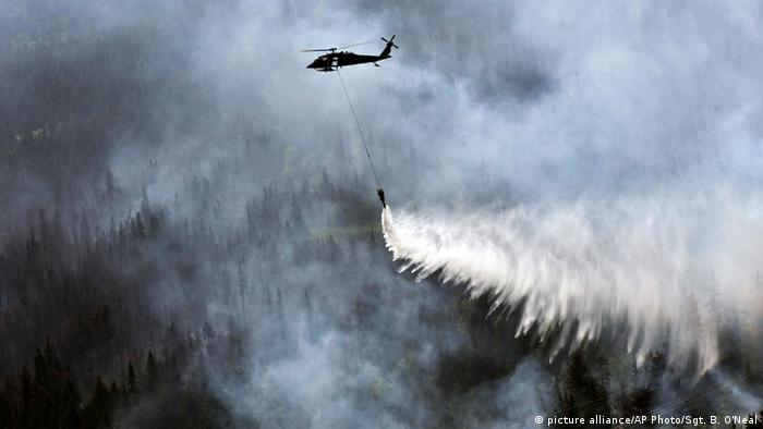 A helicopter releases water onto a fire in Alaska (Photo: U.S. Army National Guard via AP)