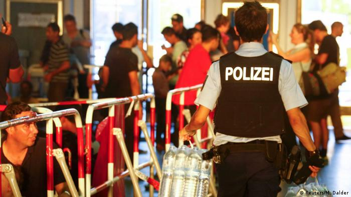 A German police officer brings water to the waiting area for migrants' registration at the railway station in Munich (photo: REUTERS/Michael Dalder)