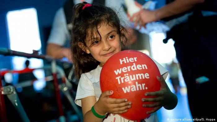 Здесь сбываются мечты - написано на шарике, который держит на вокзале в Мюнхене девочка из семьи беженцев