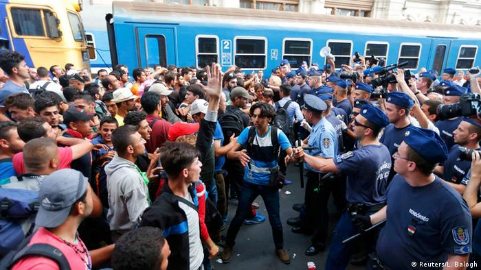 Refugees and police standing on train platform (photo: REUTERS/Laszlo Balogh)