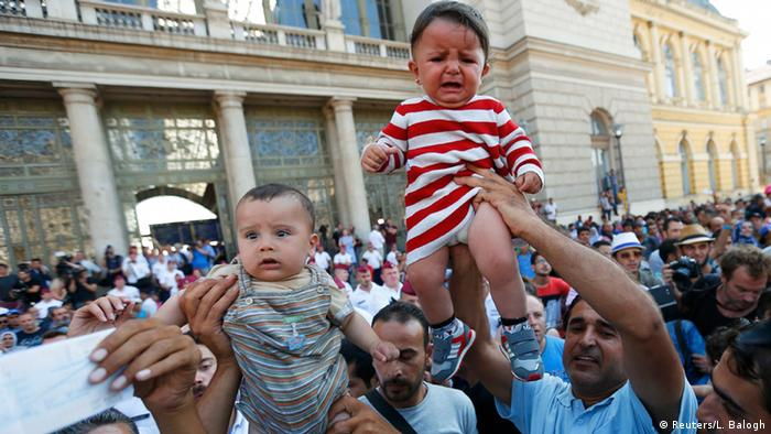 Migrants wave their train tickets and lift up children outside the main Eastern Railway station in Budapest (photo: REUTERS/Laszlo Balogh)