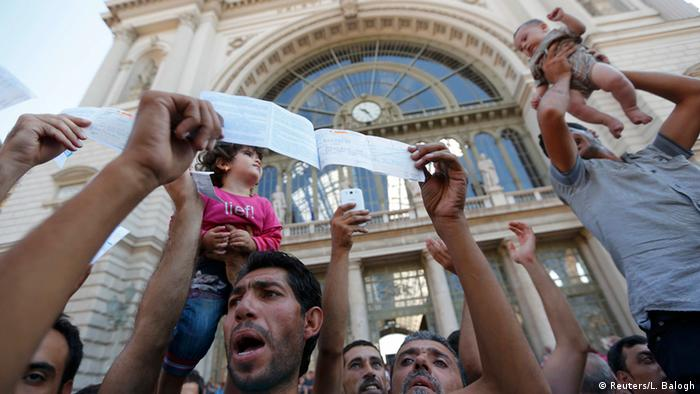 Refugees showing their tickets in front of the train station in Budapest (photo: REUTERS/Laszlo Balogh)