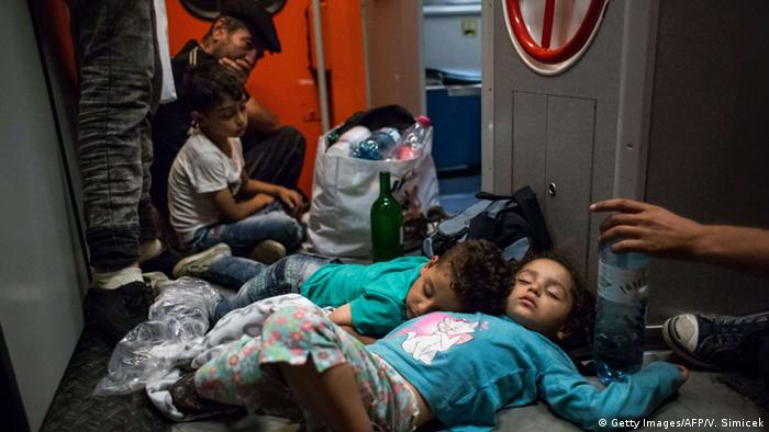Migrant children sleep on the floor on the train from Budapest to Munich (photo: Vladimir Simicek/AFP/Getty Images)