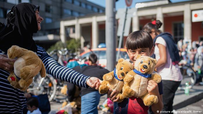 A refugee child smiles as he is handed a plush toy (photo: Nicolas Armer/dpa)