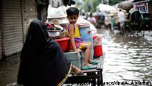 epa04907688 A woman pushes a cart with a child sitting on it down the flooded Nazim Uddin Road in Dhaka, Bangladesh, 01 September 2015. According to local reports many streets have flooded after heavy downpours in the city causing residents to suffer with stagnant rain waters as the drainage and sewage system are overwhelming the poorly maintained infrastructure. EPA/ABIR ABDULLAH