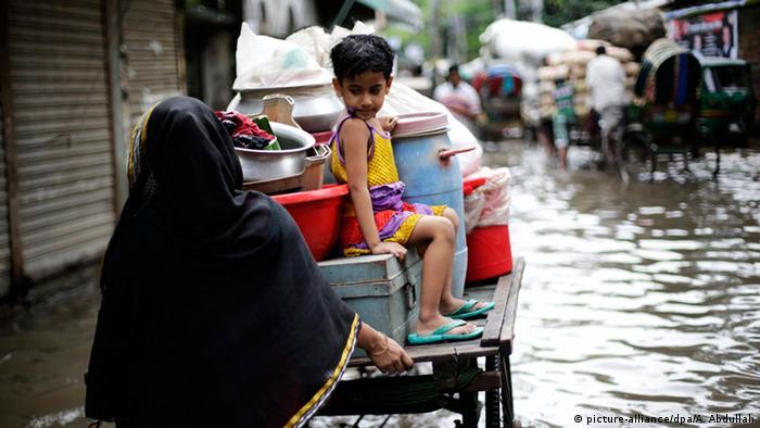 Hochwasser in Bangladesch (Dhaka). Frau schiebt ihre Habe auf einem kleinen Handwagen (Foto: EPA/ABIR ABDULLAH)